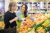 Saleswoman Showing Fresh Oranges To Female Customer