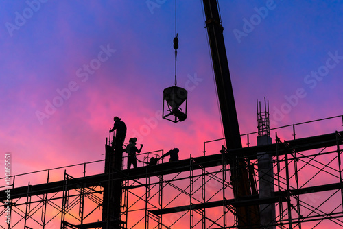 Silhouette of construction worker on scaffolding in the construction site Poster