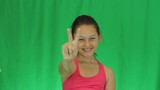 smiling girl athlete shows victory gesture on a green background