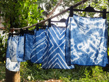 Beautiful natural indigo tie dye fabric with garden view in background. - 120923761