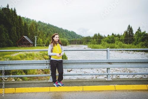 Staande foto Scandinavië Female tourist standing beside the mountain river