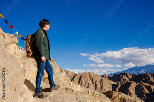 Young Asian traveler standing on high hills and looking away at the village over Poster