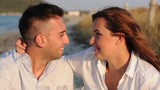 Lovely couple sitting on the beach, selective focus