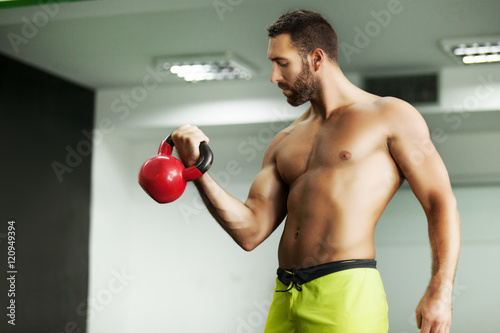 Young fit man. Training by kettle bell.