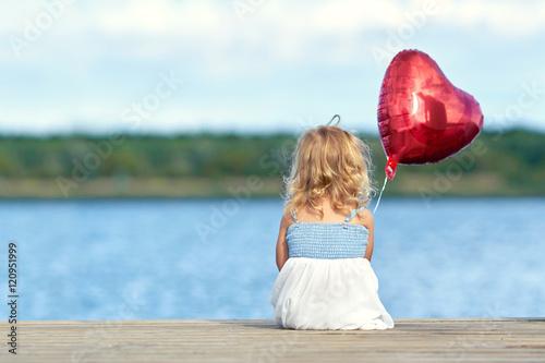Poster kleines Mädchen sitzt am Steg mit roten Ballon