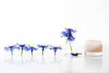 Glass jar of beauty cream and cornflowers