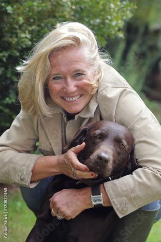Poster femme senior souriante avec chien labrador dans extérieur nature en automne