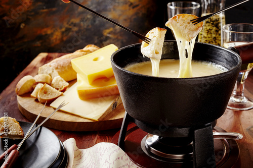 Gourmet Swiss fondue dinner on a winter evening Poster