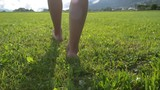 Woman walks on green lawn on a sunny summer day