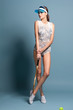 fashion female model in in swimsuit body with tennis racquet on blue background