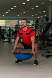 Personal Trainer Doing Exercise On Bosu Balance Ball