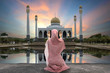Постер, плакат: Concept of religion Islam woman praying on the background of a mosque at sunset