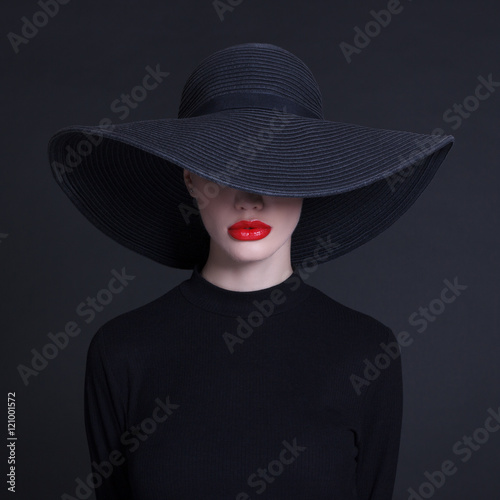 Luxury woman in a large black hat and bright lips on black background Poster