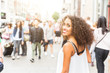 Young woman looking at camera while walking in London. Mixed race girl looking back and smiling. Blurred people on background walking on the sidewalk