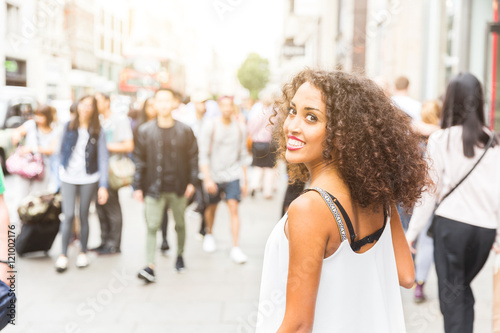 Zdjęcia na płótnie, fototapety, obrazy : Young woman looking at camera while walking in London. Mixed race girl looking back and smiling. Blurred people on background walking on the sidewalk
