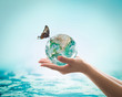 Women's hands holding green planet w/ butterfly drinking potable water from globe on turquoise blue color water background : World ocean day csr esg concept: Element of this image furnished by NASA