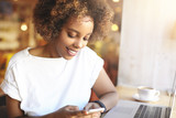 Fototapety Quick message to friend. Cute fashionable African woman holding smart phone, using photo editing applications, posting new photos via social networks,sitting in front of laptop at cafe table with mug