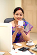 Traditional Indian business woman texting at office desk