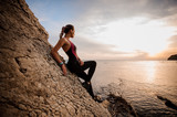 Female rock climber watching sunset over sea