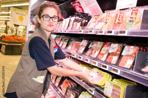 Smiling supermarket employee with glasses standing among shelves