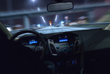 Auto fährt bei Nacht durch eine Stadt