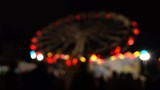 Theme park at night. Blurred spinning LED lit attraction. 4K background bokeh shot