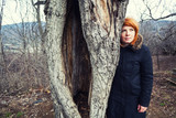 Woman standing near old tree