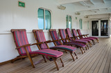 Colorful wooden deck chairs are set out for passengers on the promenade deck of a cruise ship. - 121077127