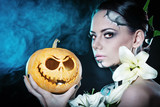 Girl with makeup for Halloween. Pumpkin