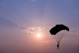 Silhouette of parachute on sunset background - 121086768