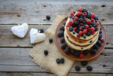 Tasty cake with strawberry, raspberry and blackberry on a wooden table