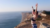 Girl standing on the cliff and raising her hands up. Аthletic beautiful woman enjoying a sunset or sunrise