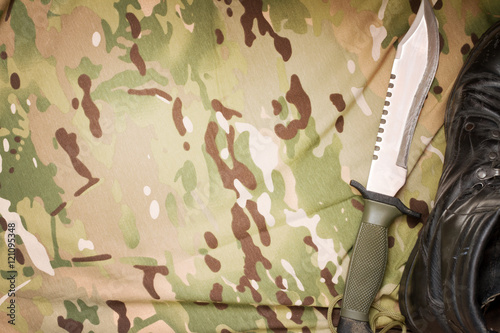 Poster Combat knife and shoes on military camouflage fabric background