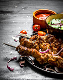 Shish kebab of pork and salad.