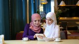 Two Beautiful Muslim Girl Using Tablet In Cafe And Laughing