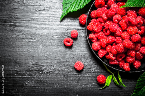 Foto Murales Wild raspberry with leaves on the old plate.