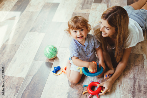 Mom playing with son on a floor