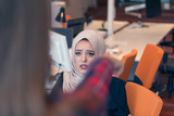 Worried arabic businesswoman wearing hijab receiving a notification from a colleague in her workplace at office