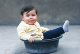 Baby boy sitting in the washbowl