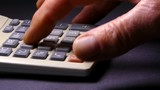 Slider shot across a man's hand using a calculator.