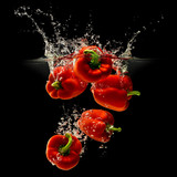 Group of bell pepper falling in water with splash on black background
