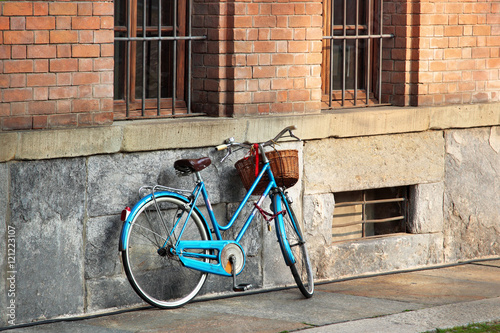 Fotobehang Fiets Bright blue bicycle on old street, Italy.