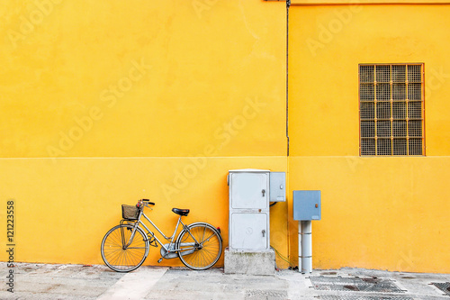 Aluminium Fiets Classic bicycle standing over wide yellow wall.