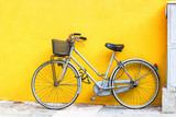 Old style bicycle parked against yellow wall. - 121223997