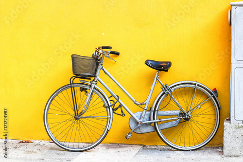 Aluminium Fiets Old style bicycle parked against yellow wall.