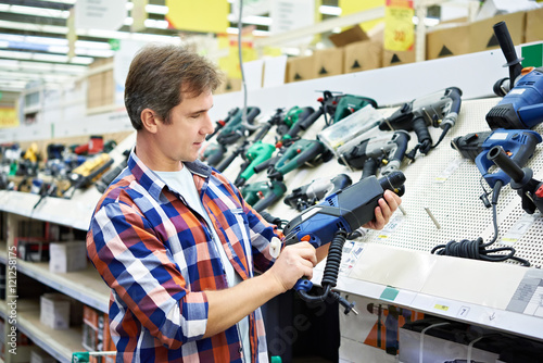 Poster Man shopping for perforator in hardware store