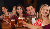Young People Group In Bar, Hold Beer Glasses Speaking, Friends Sitting At Wooden Table Chatting Pub,  Happy Smiling