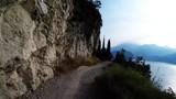Mountain biking downhill in sunny morning man over Lake Garda on path Sentiero della Ponale,  Riva del Garda, Italy,POV camera