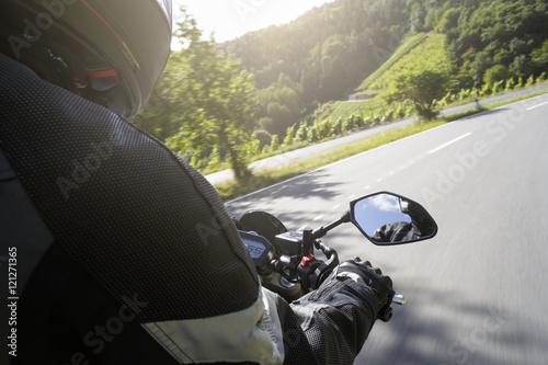 Motorradfahrer fährt auf Straße im Sommer Poster