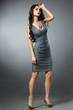 Slim woman model in a gray dress in full growth.